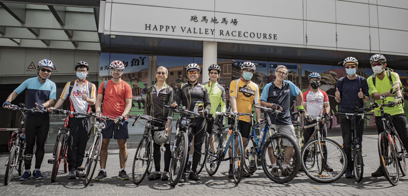 A group of brightly-clothed cyclists pose outside Hong Kong's Happy Valley Racetrack to protest lack of bicycle facilities there