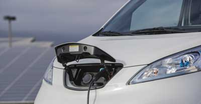 The front of a Nissan electric van, showing the charger plugged in