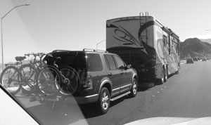 A gigantic RV towing a large SUV with bicycles on its back, along a highway in western USA