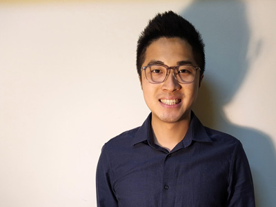 A younf architect, Benny Yip, poses against a plain white background