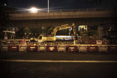 A digger sits on a highway building site at night, against a busy Hong Kong road