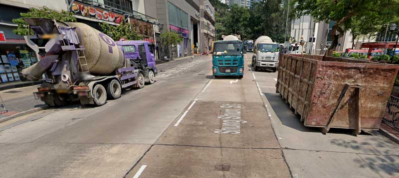 Google streetview of a busy Hong Kong junction showing construction trucks, cement mixers and an illegally parked skip