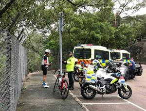 A group of police question a cyclist during an operation to improve cycle safety on Hong Kong Island - police vans and police motorbikes are lined up, while the lycra-clad cyclist on the road bike answers their questions