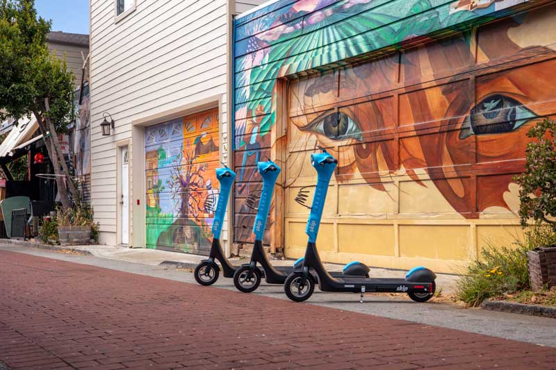 "Three bright blue Skip scooters in front of a colourful ""eyes motif"" garage door in San Francisco"