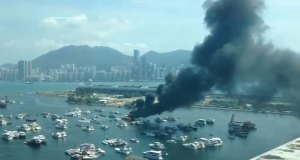 A boat burns in Kwun Tong Typhoon Shelter, Kowloon Bay