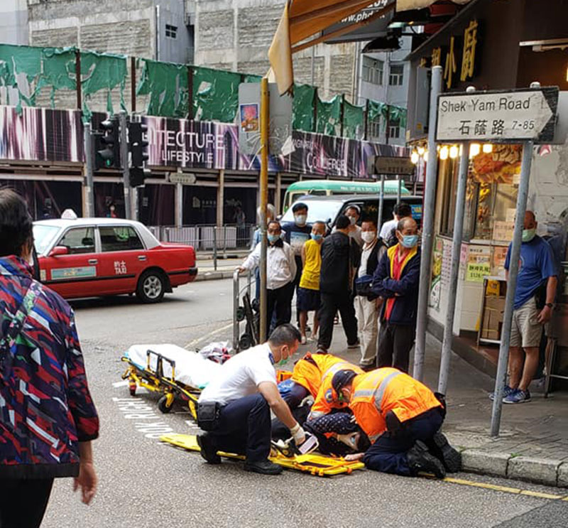 Ambulance workers work to help a lady knocked down by a van in Hong Kong