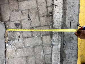 A tape measure over a pavement in Hong Kong, showing it to be narrower than 60cm