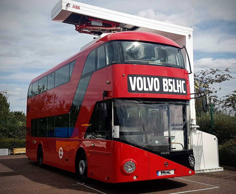 A red electric London bus from Volvo being charged from above by a pantograph developed by OppCharge