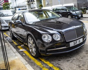 A black Bentley parked on double yellow lines outside Central Police Station in Hong Kong