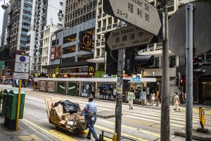 A street scene of Des Voeux Road Central in Hong Kong, with a man pushing a trolley of cardboard