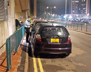 Officer from the District Trsffic Enforcement Team of Sha Tin giving a ticket to a black car parked on double yellow lines