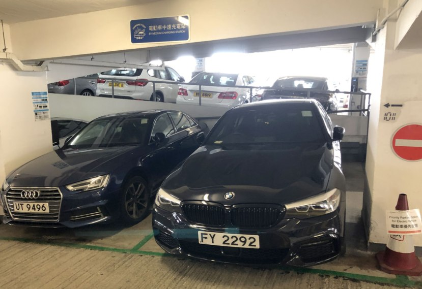 "Two petrol cars sit in the ""electric vehicle"" charging point in  Central Hong Kong car park"