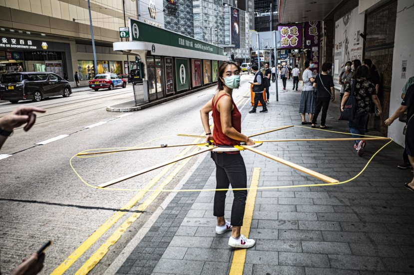 Fiona Lau of Civic Exchange walking on Des Veoux Road Central with the Social Distancing Machine