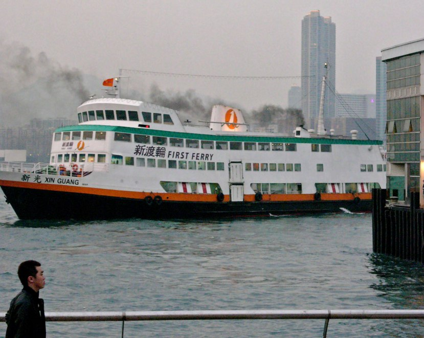 A ferry berths in Hong Kong, emitting clouds of black smoke