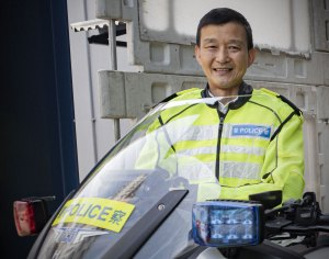 A motorcycle police officer in Hong Kong, with yellow hi-vis jacket behind his motorbike