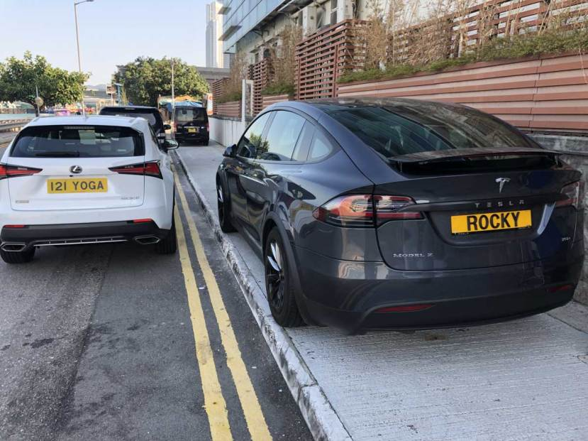 A grey Tesla parks on the pavement in Hong Kong