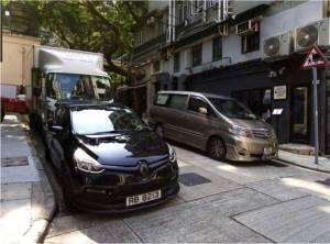 Vans and a truck line a charming Hong Kong lane