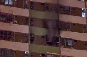 Smoke pours from a high-rise apartment in a fire thought to be started by a charging e-scooter - a seven year old boy died in the blaze