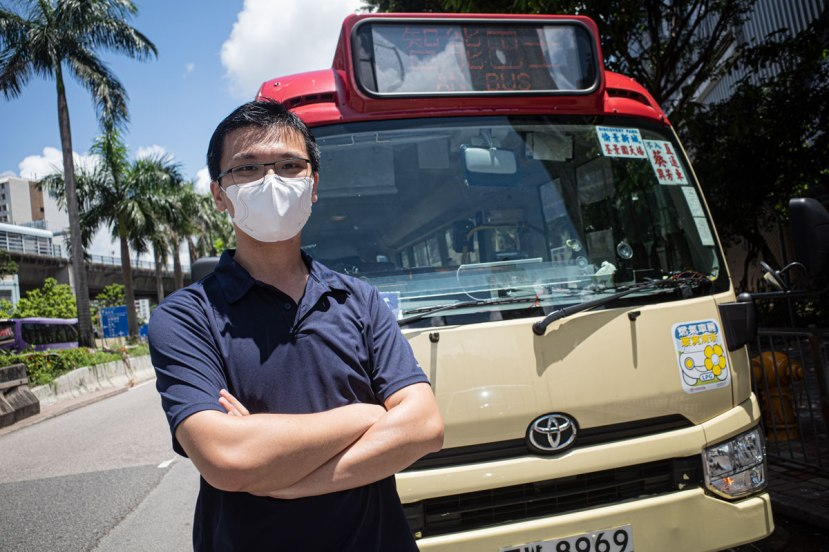 Founder of red minibus firm AN Bus, Franki Lee, stands in front of one of his trhee buses on a sunny day with palm trees in the background