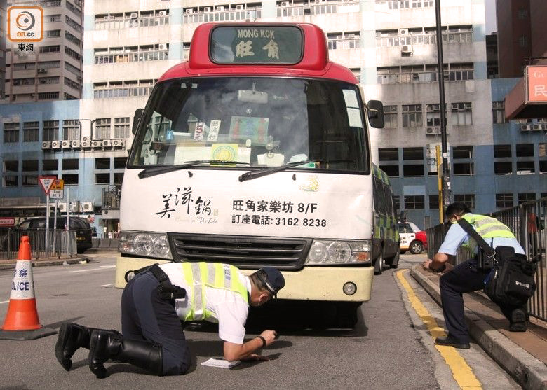 Police search underneath a red minibus in Hong Kong after a man was knocked down and killed by the vehicle