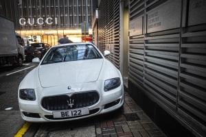 A Maserati blocks a pavement in Hong Kong in front of a Gucci store
