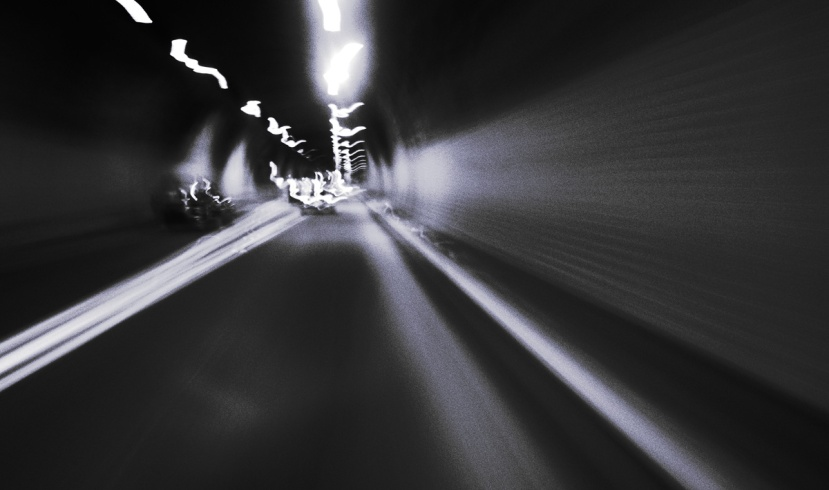 An abstract image of a high-speed pursuit through a tunnel, showing the road and blurred lights