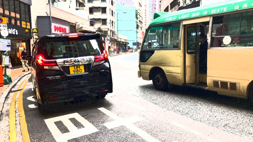 A green minibus stops in the middle of the road as thge bus stop is blocked by an idling van
